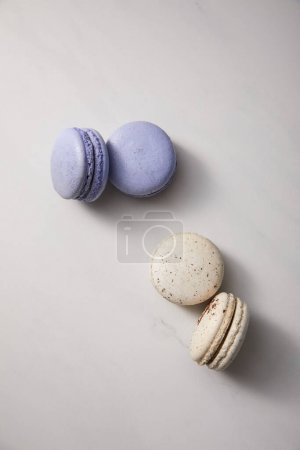 Photo for Top view of assorted delicious violet and white  french macaroons on grey background - Royalty Free Image