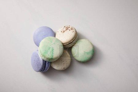 Photo pour Vue de dessus de macarons verts, violets et blancs sur fond gris - image libre de droit