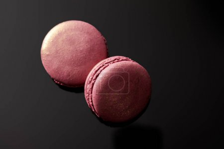Photo for Top view of shiny pink french macaroons on black background - Royalty Free Image