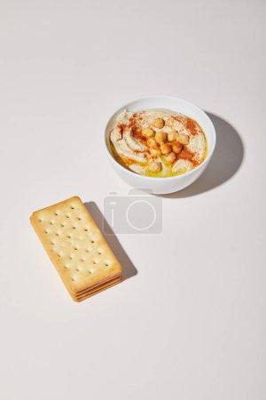Schüssel mit leckerem Hummus und Crackern auf grauem Hintergrund