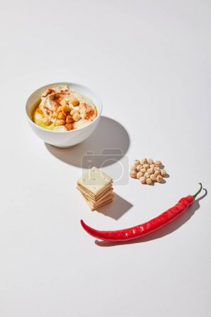 Bowl with tasty hummus near crackers, chili pepper and chickpea on grey background