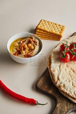 Photo pour Bol avec houmous, craquelins, pain pita et légumes sur planche à découper sur fond gris - image libre de droit