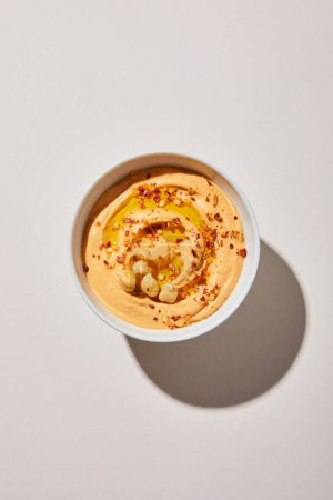 Top view of bowl with delicious hummus on grey background
