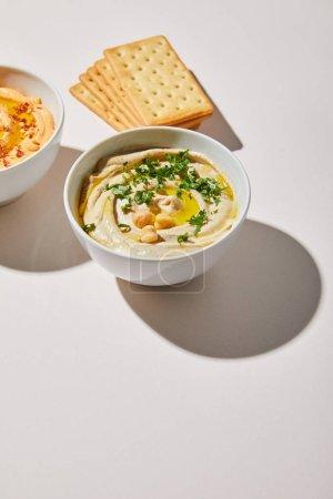 Schalen mit leckerem Hummus und Crackern auf grauem Hintergrund