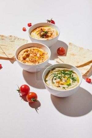 Schalen mit köstlichem Hummus, reifen Kirschtomaten und Fladenbrot auf grauem Hintergrund