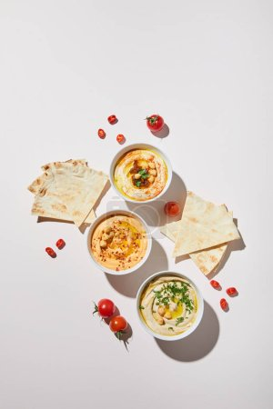Photo for Top view of bowls with delicious hummus, ripe vegetables and pita bread on grey background - Royalty Free Image