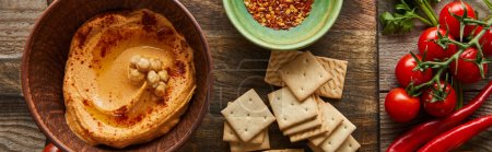 Photo for Top view of crackers, bowls with spices and hummus on cutting board with vegetables on wooden background, panoramic shot - Royalty Free Image