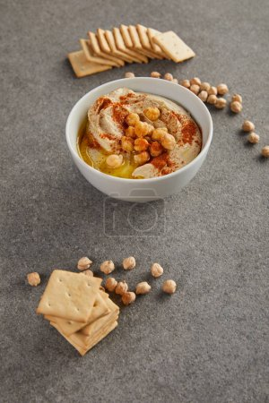 Delicious hummus in bowl with chickpea and crackers on grey background