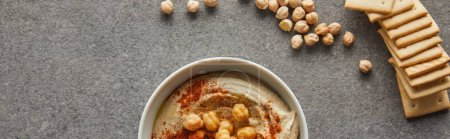 Top view of bowl with delicious hummus, chickpea and crackers on grey background, panoramic shot