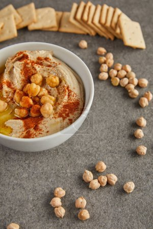 Selective focus of bowl with tasty hummus, chickpea and crackers on grey background