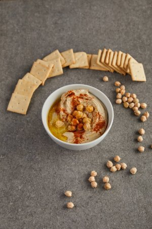 Photo for Bowl with tasty hummus, chickpea and crackers on grey - Royalty Free Image