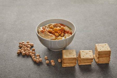 Photo pour Bol avec houmous délicieux, pois chiches et craquelins sur gris - image libre de droit