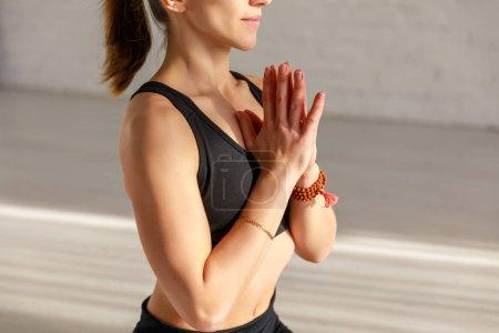 Photo pour Vue recadrée de la femme avec les mains priantes dans le studio de yoga - image libre de droit