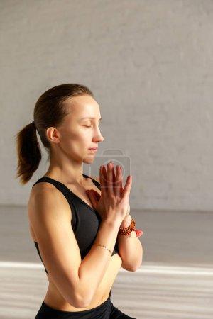 Photo pour Femme attrayante avec les yeux fermés et les mains priantes dans le studio de yoga - image libre de droit