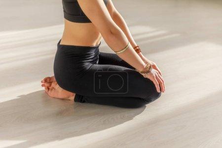 Photo pour Vue recadrée de la femme avec pieds nus faisant exercice seiza sur le sol dans le studio de yoga - image libre de droit