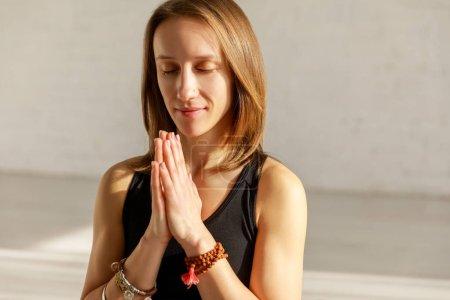 Photo pour Femme heureuse avec les mains priantes dans le studio de yoga - image libre de droit