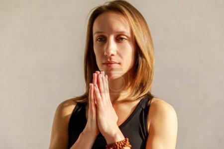 Photo pour Belle femme avec des mains priantes dans le studio de yoga - image libre de droit