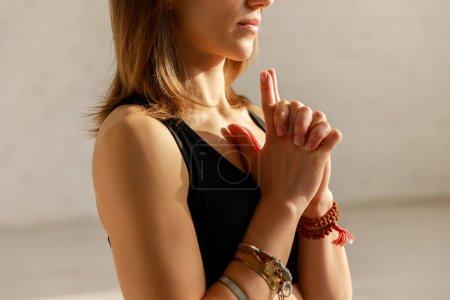 Photo pour Vue recadrée de la femme avec les mains serrées dans le studio de yoga - image libre de droit