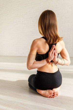 Photo pour Vue arrière de la femme avec pieds nus dans la pose de prière inverse dans le studio de yoga - image libre de droit