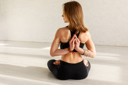 Photo for Attractive woman in reverse prayer pose practicing yoga - Royalty Free Image