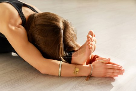 Photo for Woman with barefoot stretching on floor in yoga studio - Royalty Free Image