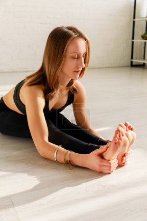 Photo for Attractive woman with closed eyes stretching on floor in yoga studio - Royalty Free Image