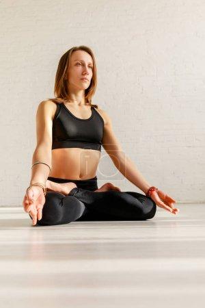Photo pour Jeune femme avec pieds nus pratiquant le yoga - image libre de droit