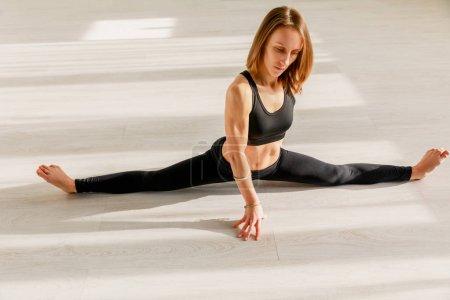 Photo pour Attrayant femme faire ficelle étirement sur le sol - image libre de droit