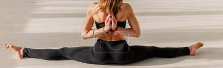 Photo for Panoramic shot of woman in reverse prayer pose doing twine stretching on floor - Royalty Free Image