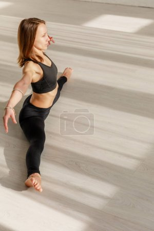 Photo for Attractive woman with outstretched hands doing twine stretching on floor - Royalty Free Image