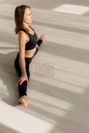 Photo pour Flexible et jeune femme faisant ficelle étirement sur le sol - image libre de droit