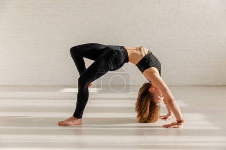 Photo pour Femme flexible faisant la pose de roue dans le studio de yoga - image libre de droit