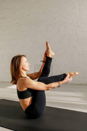 Photo pour Femme flexible étirant les jambes tout en étant assis sur le tapis de yoga - image libre de droit