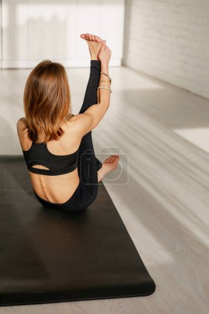 Photo for Back view of woman stretching leg while sitting on yoga mat - Royalty Free Image