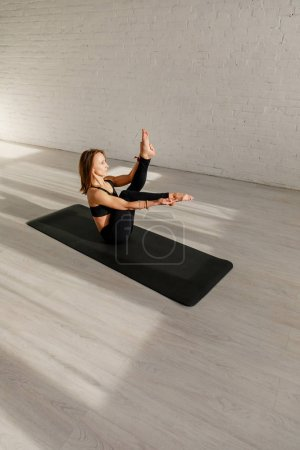 Photo for Attractive woman stretching legs while sitting on yoga mat near brick wall - Royalty Free Image