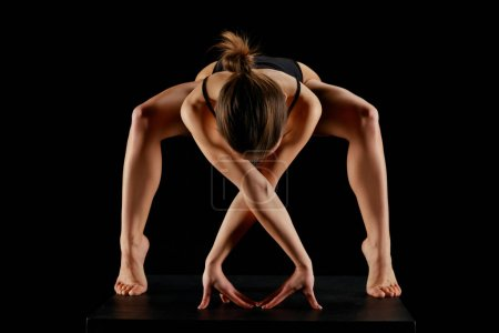 Photo for Woman standing on tip toe while practicing yoga isolated on black - Royalty Free Image