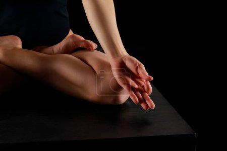 Photo pour Vue recadrée de la femme en pose de lotus pratiquant le yoga isolé sur noir - image libre de droit