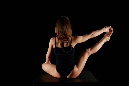 back view of woman stretching leg isolated on black