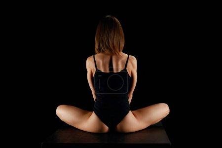 Photo pour Vue arrière de fille dans la pose de lotus isolé sur noir - image libre de droit