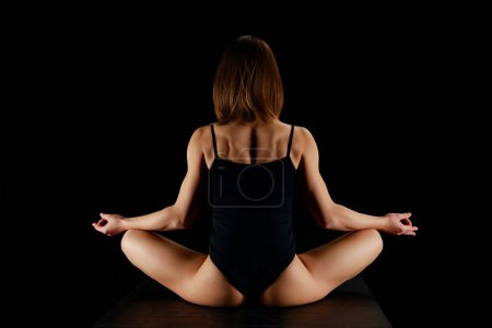 Photo pour Back view of girl in lotus pose meditating isolated on black - image libre de droit
