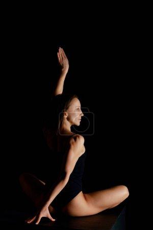 Photo pour Jolie femme en pose de lotus pratiquant le yoga isolé sur noir - image libre de droit