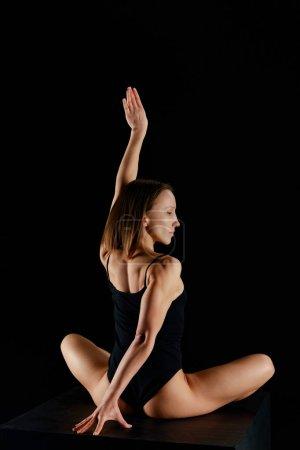 Photo pour Fille en pose de lotus avec la main tendue pratiquant le yoga isolé sur noir - image libre de droit
