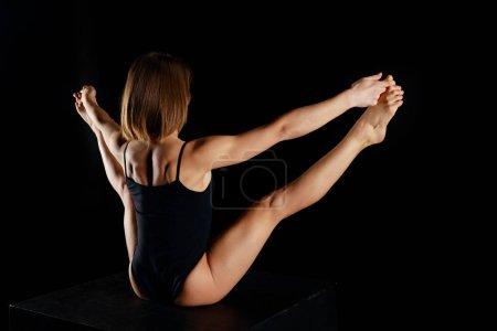 Photo pour Vue arrière de la femme en body pratiquant le yoga isolé sur noir - image libre de droit