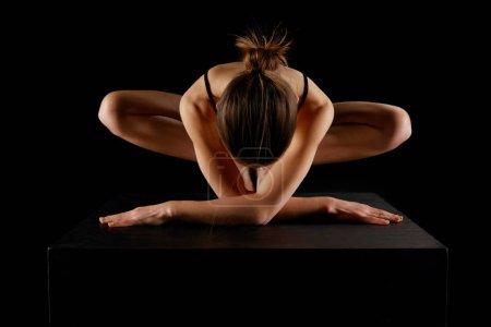 Foto de Joven deportista practicando yoga aislado en negro - Imagen libre de derechos