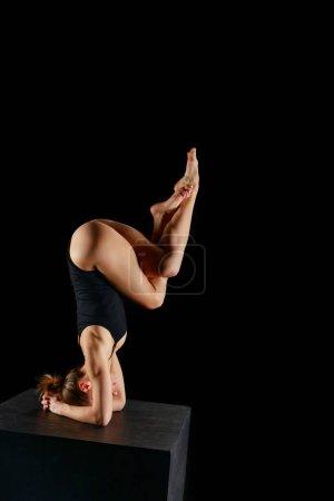 Photo pour Femme en bodysuit faisant l'exercice de main d'aigle jambes isolé sur noir - image libre de droit