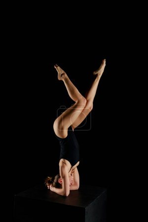 Photo for Attractive girl with barefoot doing yoga headstand exercise isolated on black - Royalty Free Image