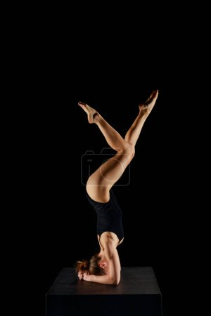 Photo for Girl with barefoot doing yoga headstand exercise isolated on black - Royalty Free Image