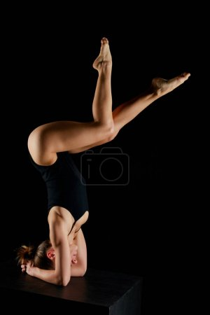 Photo for Woman in bodysuit doing yoga headstand exercise isolated on black - Royalty Free Image