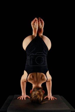 Photo pour Vue arrière de fille en body faisant yoga exercice de tête isolé sur noir - image libre de droit
