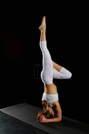 Photo for Girl in white sportswear doing yoga handstand exercise isolated on black - Royalty Free Image